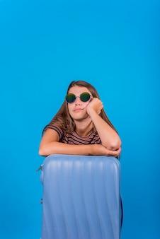 Jonge vrouw die en op koffer mist leunt