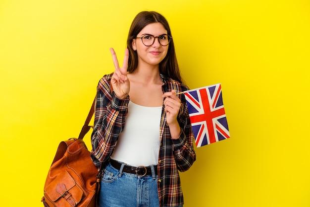 Jonge vrouw die engels bestudeert geïsoleerd op roze muur die nummer twee met vingers toont