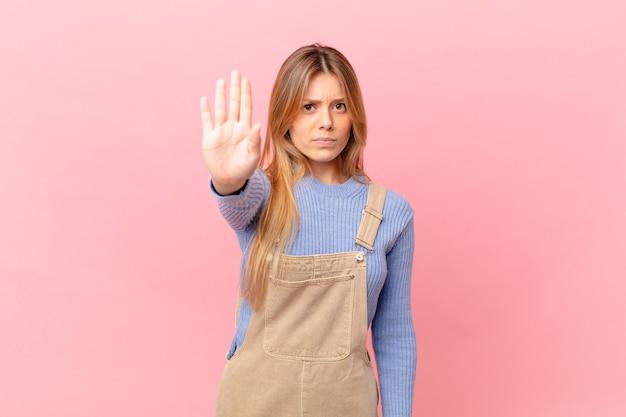 Jonge vrouw die er serieus uitziet en open palm toont die een stopgebaar maakt
