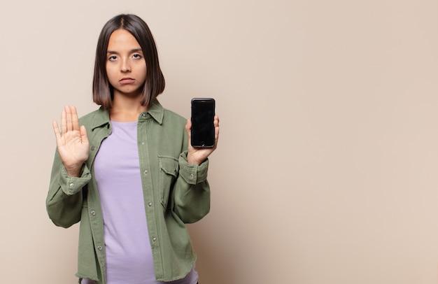 Jonge vrouw die ernstig, streng, ontevreden en boos kijkt die open palm toont die stopgebaar maakt