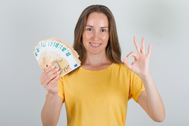 Jonge vrouw die eurobankbiljetten met ok teken in geel t-shirt houdt en gelukkig kijkt