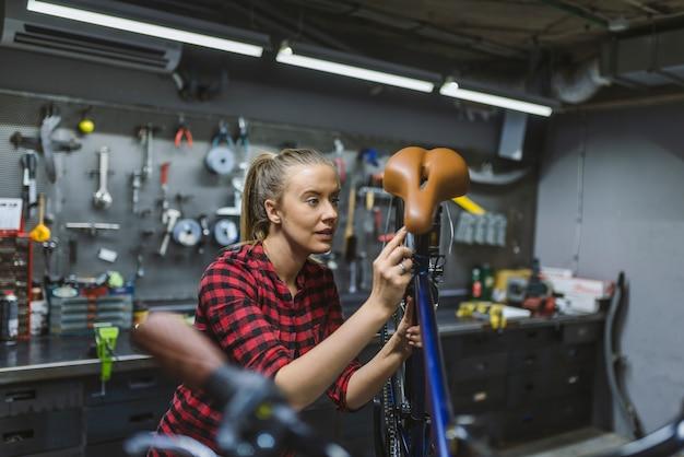 Jonge vrouw die fietsketting aanpast en fiets herstelt
