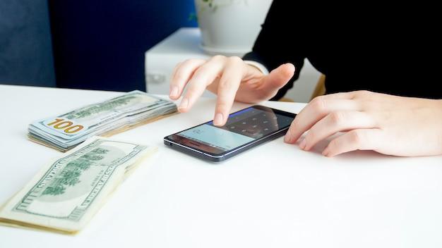Jonge vrouw die financieel budget plant en rekenmachine op smartphone gebruikt.