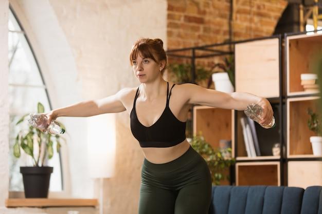 Jonge vrouw die fitness aërobe yoga thuis uitoefent sportieve levensstijl die actief wordt tijdens lockdown