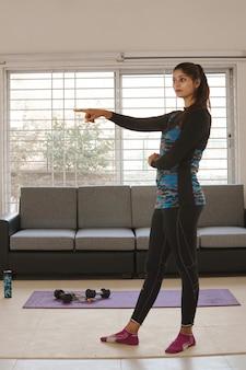 Jonge vrouw die fitnessyoga uitoefent, een levensstijl die actief wordt tijdens de lockdown