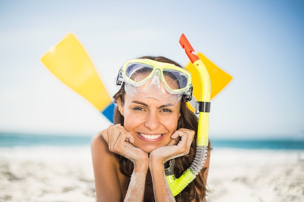 Jonge vrouw die flippers draagt bij het strand