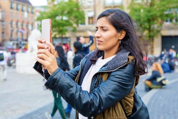 Jonge vrouw die foto in de stad neemt