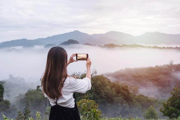 Jonge vrouw die foto met smartphone neemt