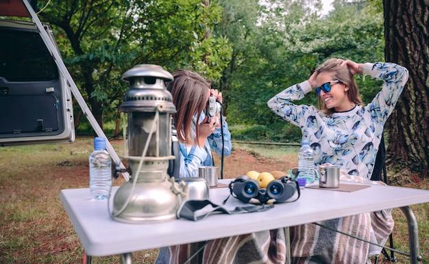 Jonge vrouw die foto neemt naar gelukkige vriend met handen in haar hoofd boven een natuur