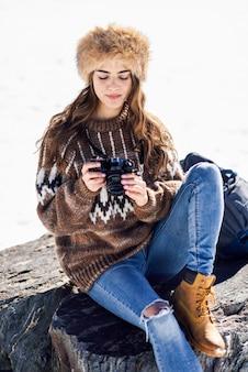 Jonge vrouw die foto's in de sneeuwbergen neemt