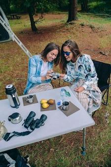 Jonge vrouw die foto's maakt naar een gelukkige vriend tijdens het ontbijt op de camping