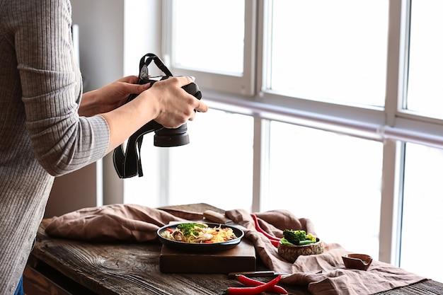 Jonge vrouw die foto's maakt van voedsel in professionele studio
