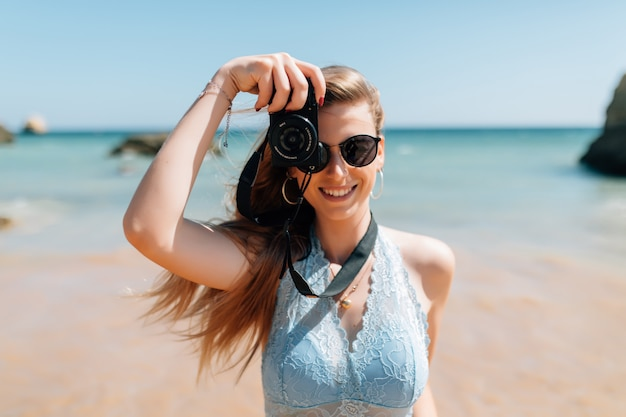 Jonge vrouw die foto's met fotocamera op het strand neemt