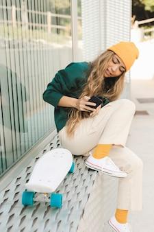 Jonge vrouw die foto's van skateboard neemt
