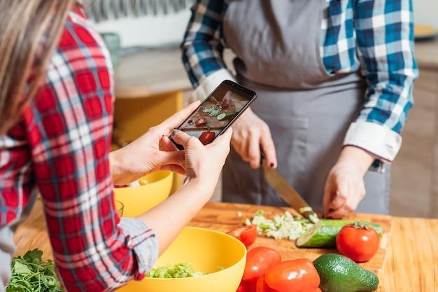 Jonge vrouw die foto van een andere dame in keuken neemt tijdens het koken