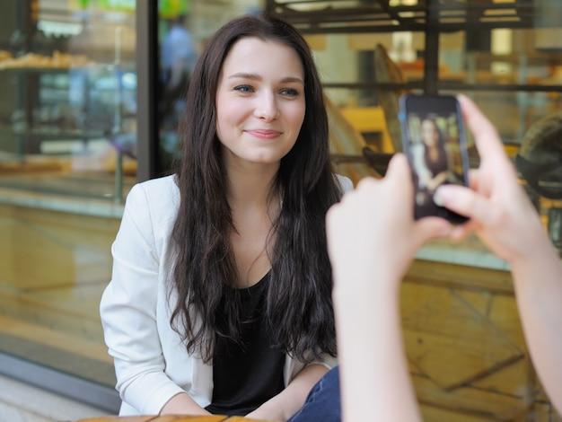 Jonge vrouw die foto van haar vriend neemt