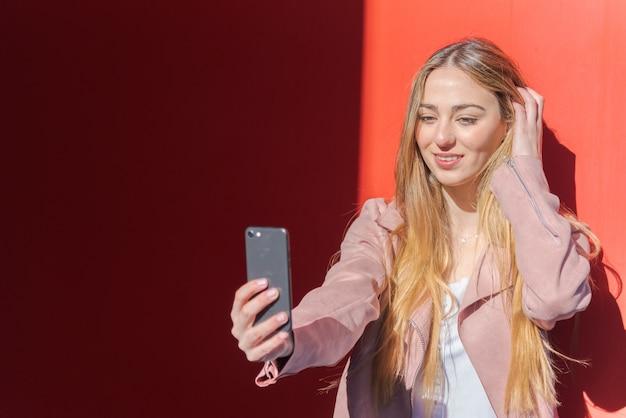 Jonge vrouw die fotograferen met mobiel op rood