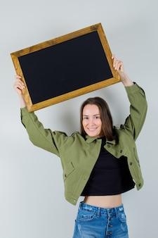 Jonge vrouw die frame boven het hoofd in groene jas, vooraanzicht opheft.