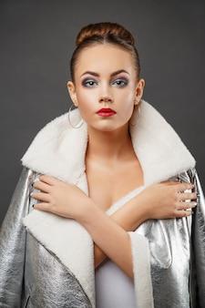 Jonge vrouw die futuristisch zilveren fahionjasje draagt