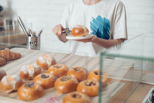 Jonge vrouw die gebak op witte plaat plaatst