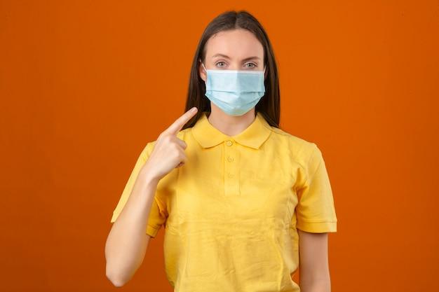 Jonge vrouw die geel poloshirt in beschermend medisch masker draagt dat met vinger op haar masker met ernstig gezicht richt dat camera bekijkt die zich op oranje achtergrond bevindt