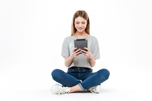 Jonge vrouw die geïsoleerde tablet gebruiken