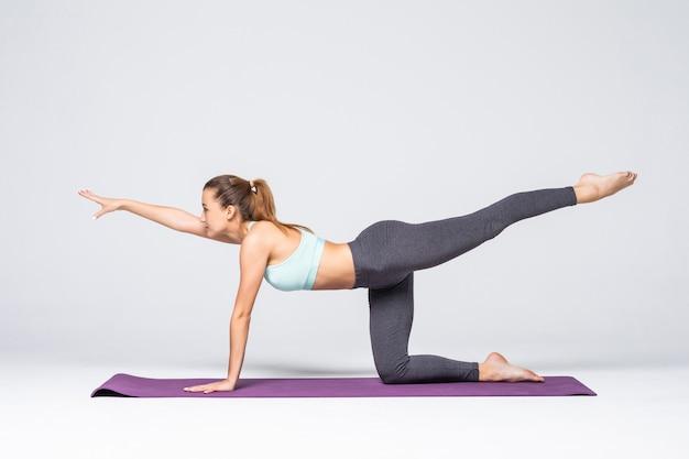 Jonge vrouw die geïsoleerde yogaoefening doet