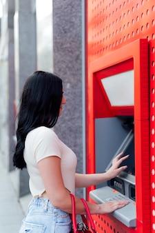 Jonge vrouw die geld opneemt bij atm