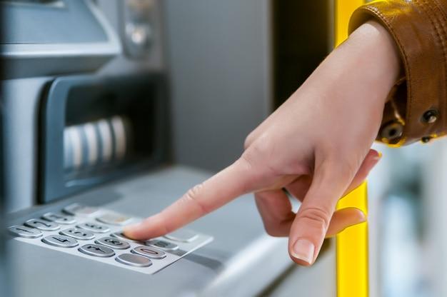 Jonge vrouw die geld terugtrekt bij creditcard bij geldautomaat