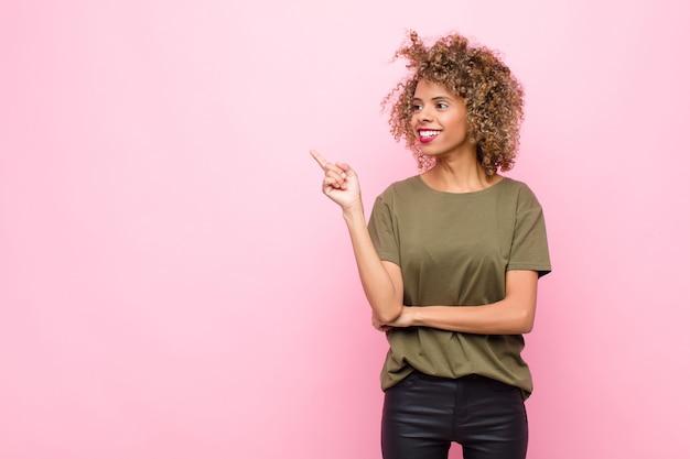 Jonge vrouw die gelukkig glimlacht en zijdelings kijkt, zich afvraagt, of een idee over roze muur denkt heeft