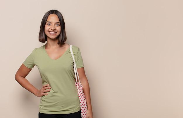 Jonge vrouw die gelukkig glimlacht met een hand op heup en zelfverzekerde, positieve, trotse en vriendelijke houding