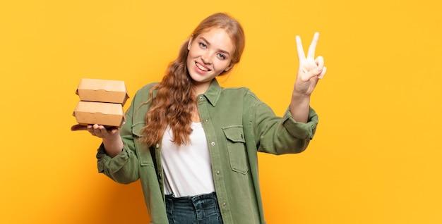 Jonge vrouw die gelukkig, zorgeloos en positief glimlacht en kijkt, overwinning of vrede met één hand gebaart