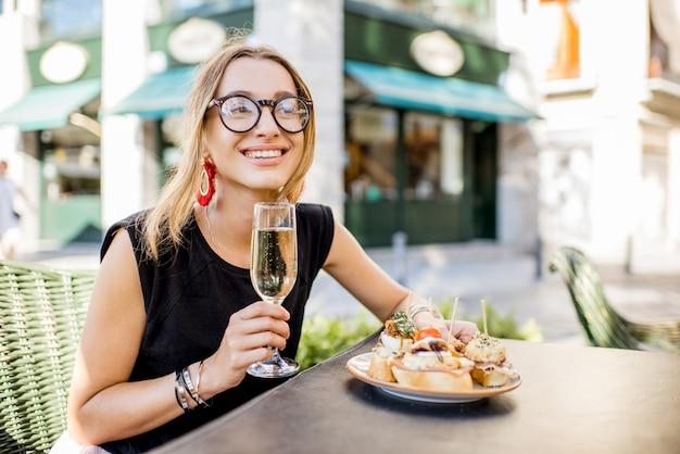 Jonge vrouw die geniet van een smakelijk voorgerecht met pinchos, traditionele spaanse snack en een glas wijn die buiten aan de bar in de stad valencia zit