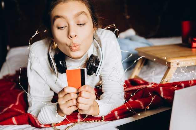 Jonge vrouw die geniet van online winkelen voor kerstmis