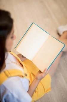 Jonge vrouw die geopend boek in blauwe dekking houdt