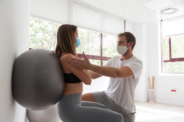 Jonge vrouw die geschiktheidsbal en pilatesoefening doet met coach die masker draagt tijdens covid-19