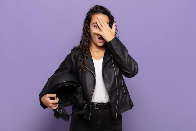 Jonge vrouw die geschokt, bang of doodsbang kijkt, gezicht bedekt met hand en tussen vingers gluurt