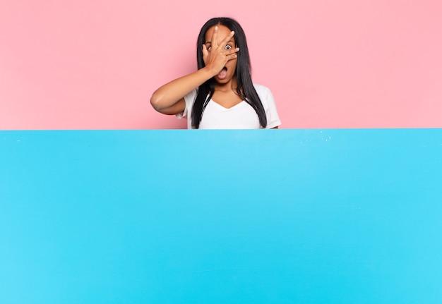 Jonge vrouw die geschokt, bang of doodsbang kijkt, haar gezicht bedekt met de hand en tussen de vingers gluurt