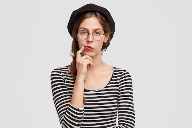 Jonge vrouw die gestreept overhemd en baret draagt