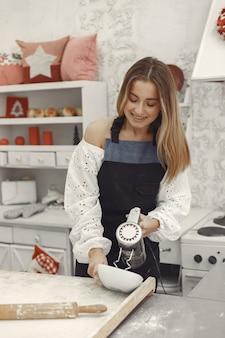 Jonge vrouw die gevormde koekjes maakt