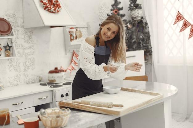 Jonge vrouw die gevormde koekjes voor kerstmis maakt.
