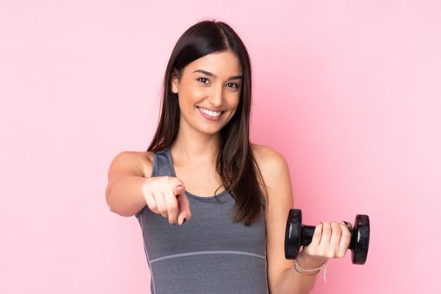 Jonge vrouw die gewichtheffen geïsoleerd op roze muur maakt vinger op u met een zekere uitdrukking richt