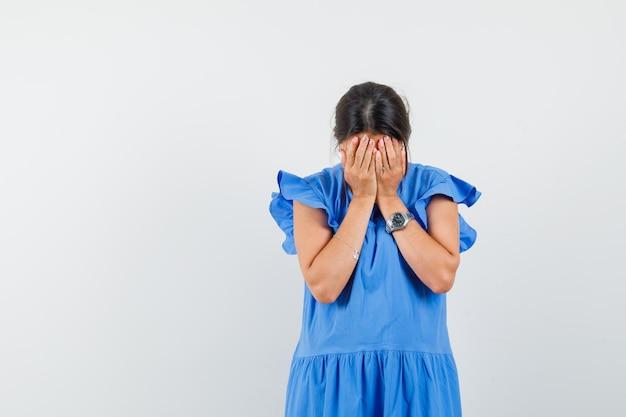 Jonge vrouw die gezicht bedekt met handen in blauwe jurk en boos kijkt