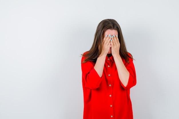 Jonge vrouw die gezicht bedekt met handen in rode blouse en depressief kijkt, vooraanzicht.