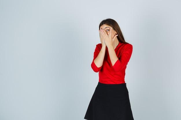 Jonge vrouw die gezicht behandelt met handen, die door vingers in rode blouse kijken