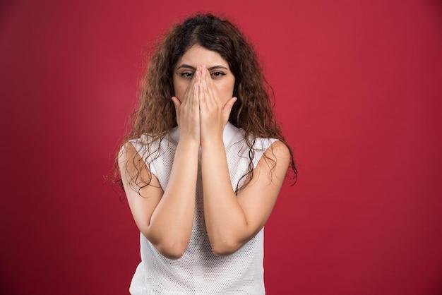 Jonge vrouw die gezicht behandelt met handen op rode studiomuur.