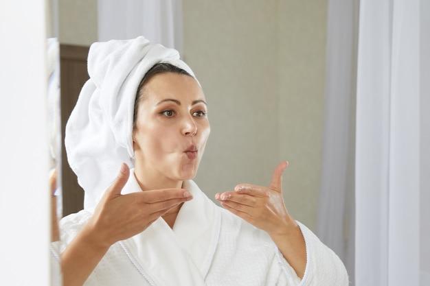 Jonge vrouw die gezichtsgymnastiek doet, zelfmassage en verjongende oefeningen voor het opbouwen van de huid