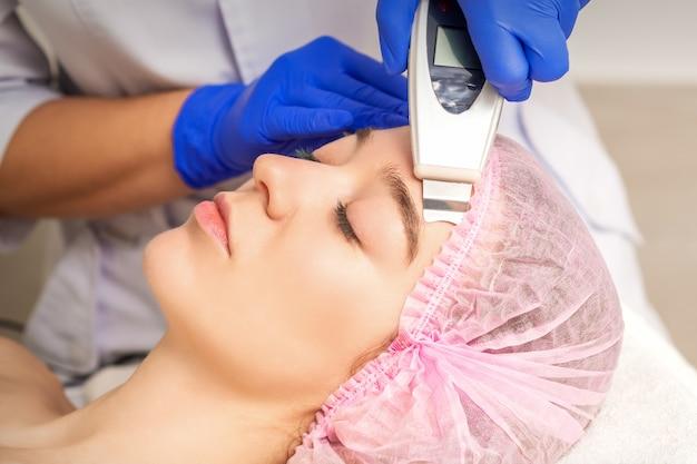 Jonge vrouw die gezichtshuid schoonmaken door ultrasone apparatuur in medische salon ontvangt
