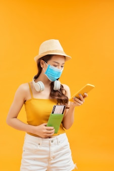 Jonge vrouw die gezichtsmasker draagt dat smartphone gebruikt en paspoort houdt