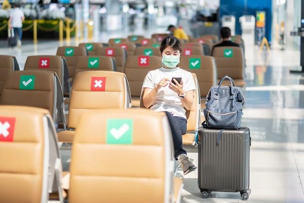 Jonge vrouw die gezichtsmasker draagt en mobiele smartphone gebruikt in luchthaven, bescherming coronavirus-infectie (covid-19), aziatische vrouwenreiziger zittend op een stoel. nieuw normaal en sociaal afstand nemen